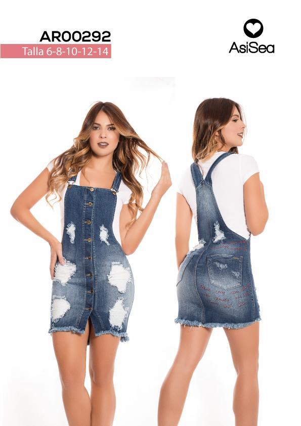 Overol falda en tono índigo medio con destroyed , ruedo desflecad, botones en frente, bolsillos traseros y aplique atrás